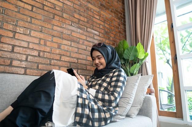 Donna felice che per mezzo del suo telefono cellulare Foto Premium