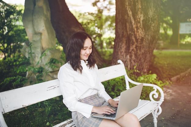 Felice giovane studentessa asiatica in un parco che lavora al computer portatile Foto Premium