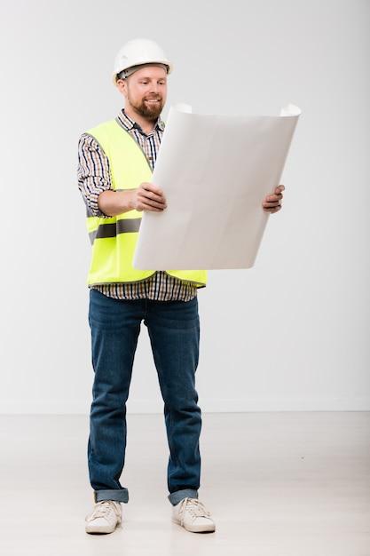 Felice giovane costruttore barbuto in elmetto protettivo bianco, jeans, camicia a scacchi e giubbotto giallo guardando il progetto davanti alla telecamera Foto Premium