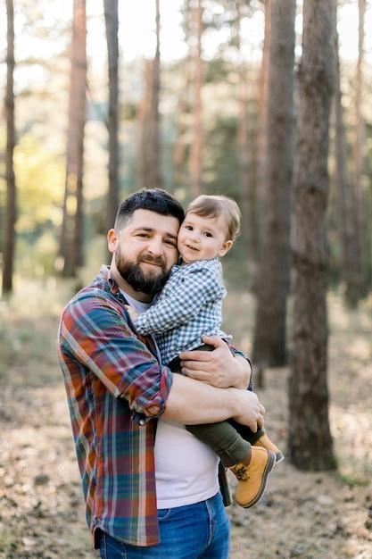 Felice giovane barbuto papà che tiene suo figlio, ragazzino divertente ragazzino, guardando la fotocamera mentre si cammina insieme in un parco o foresta al giorno pieno di sole Foto Premium