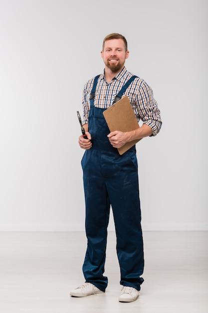 Felice giovane meccanico barbuto in tuta e camicia che tiene appunti con documento e sgabello mentre si trova in isolamento Foto Premium