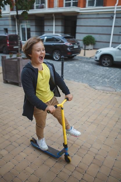 Felice giovane ragazzo godendo in sella a uno scooter per le strade della città Foto Premium