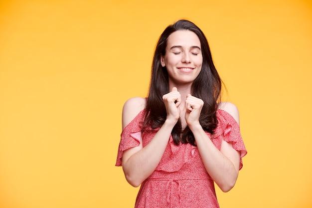 Felice giovane donna bruna in abito rosso tenendo gli occhi chiusi con le mani dal collo sopra la parete gialla Foto Premium