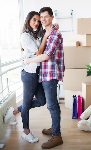 Giovani coppie felici che si muovono insieme nel nuovo appartamento Foto Premium