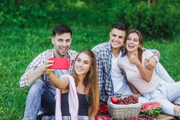 Giovani amici felici che hanno picnic nel parco. sono tutti felici, si divertono insieme. Foto Premium
