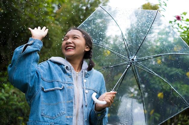 Ragazza felice che gioca con la pioggia nel giardino verde. Foto Premium