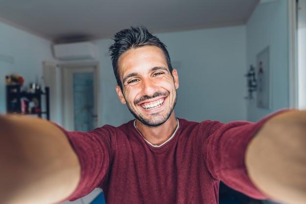 Felice giovane bello millenario prendendo un selfie sorridente nel soggiorno di casa. Foto Premium