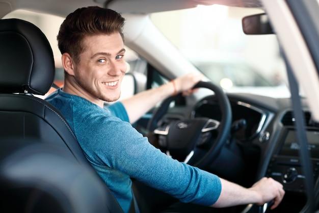 Giovane driver maschio felice al volante Foto Premium