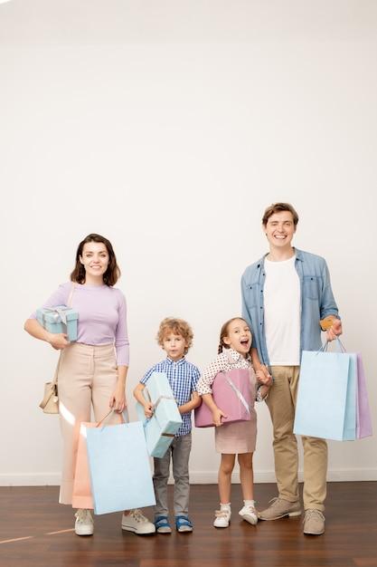 Giovani genitori felici con sacchetti di carta e due bambini piccoli con scatole regalo che sembrano soddisfatti della vendita del venerdì nero Foto Premium