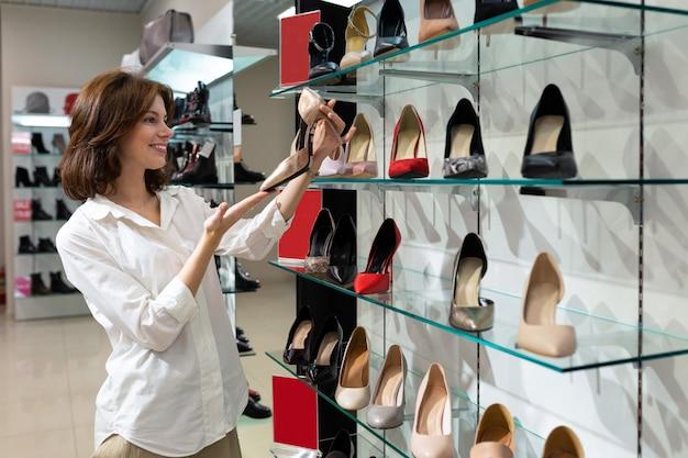 La giovane donna felice esamina le paia delle scarpe in sua mano Foto Premium