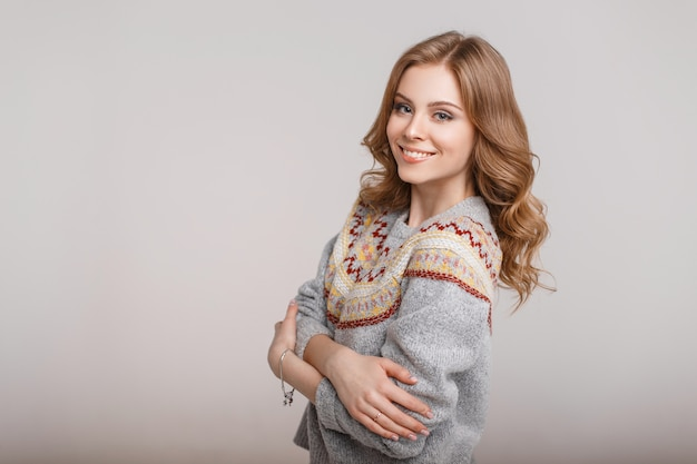 Felice giovane donna in un maglione elegante alla moda su uno sfondo grigio Foto Premium