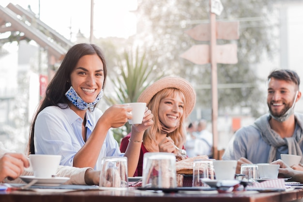 Felice giovane donna che indossa la maschera per il viso sorridente al ristorante Foto Premium