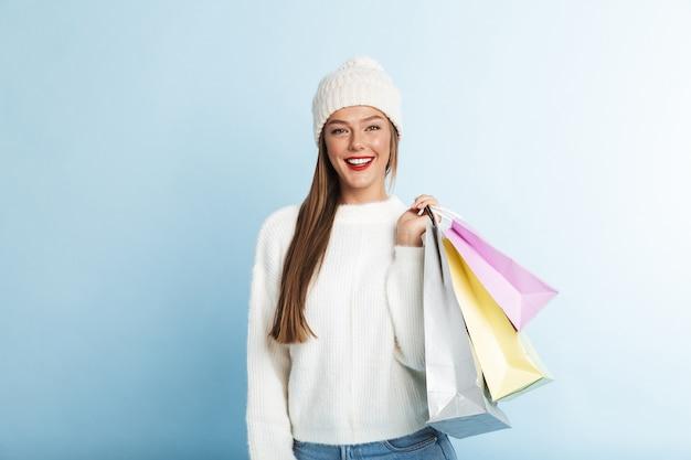Felice giovane donna che indossa un maglione, portando le borse della spesa Foto Premium
