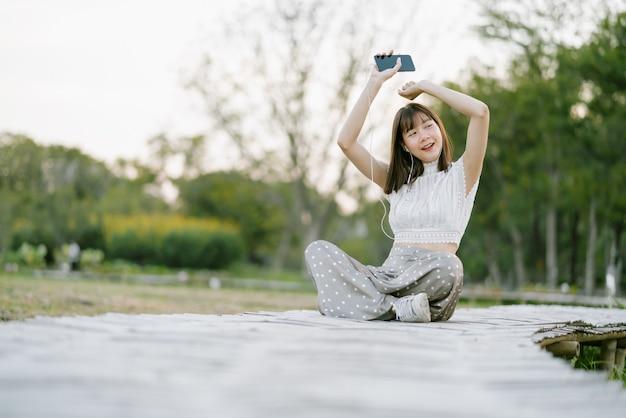 Felice giovane donna in abiti bianchi con auricolari seduto sul passaggio pedonale in legno nel parco e divertirsi mentre si utilizza il telefono cellulare ascoltando musica con gli occhi aperti guardando lontano dalla fotocamera Foto Premium