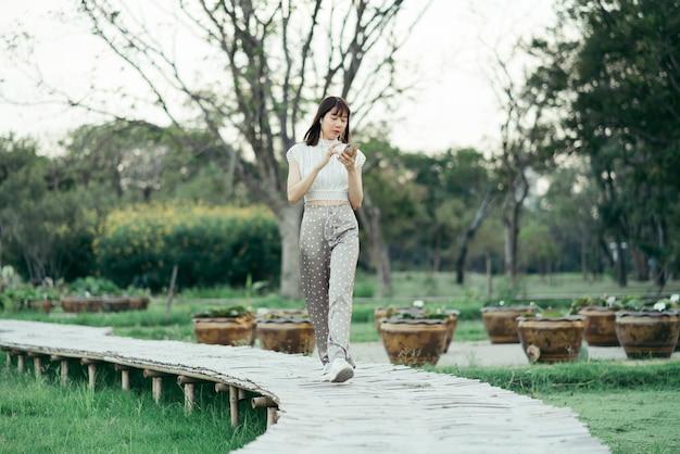 Felice giovane donna in abiti bianchi con auricolari utilizzando il telefono cellulare ascoltando musica con gli occhi guardando lo schermo godendo il suo momento mentre passeggia sulla passerella in legno nel parco Foto Premium