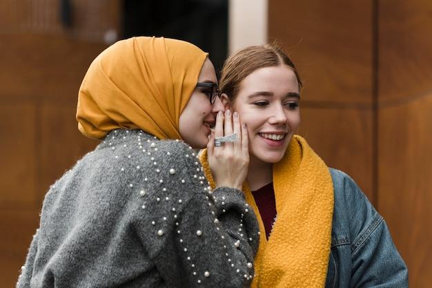 Giovani donne felici che bisbigliano l'un l'altro Foto Premium
