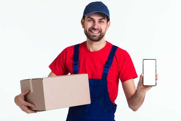 Uomo del corriere del lavoratore duro che mostra telefono cellulare e scatola Foto Premium