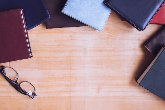 Libri con copertina rigida con occhiali sulla tavola di legno. spazio libero per il testo Foto Premium