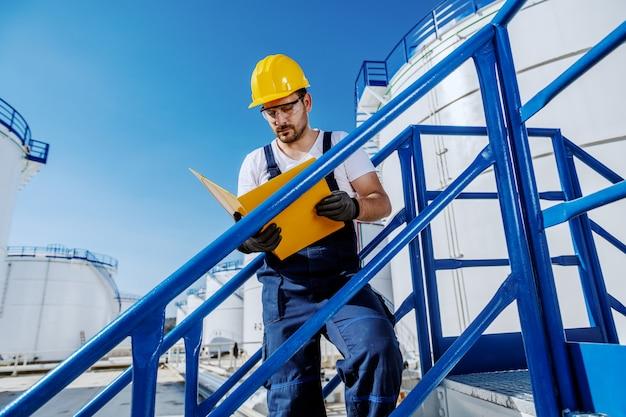 Lavoratore caucasico bello laborioso in generale e con il casco sulla testa che sta sulle scale e che esamina cartella con i documenti. produzione di olio. Foto Premium