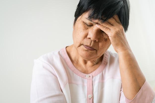 Mal di testa, stress, emicrania dell'anziana, problema sanitario del concetto senior Foto Premium