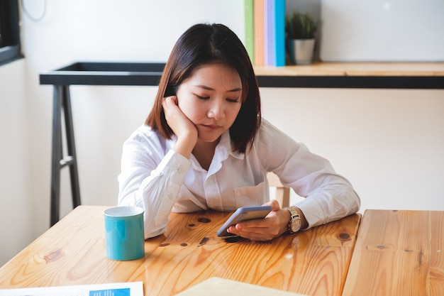Headshot di donna annoiata nel business casual utilizzando e guardando sullo smart phone Foto Premium