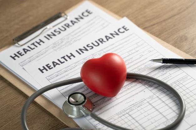 Assicurazione sanitaria negli appunti, nello stetoscopio e nel cuore Foto Premium