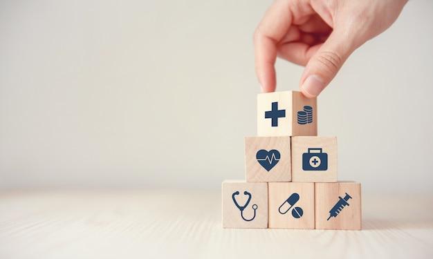 Il concetto dell'assicurazione malattia, riduce le spese mediche, il cubo di legno di vibrazione della mano con l'assistenza sanitaria dell'icona medica e la moneta su fondo di legno, spazio della copia. Foto Premium