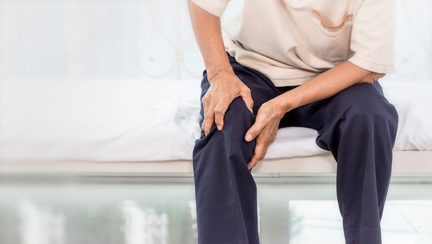 Concetto di problema di salute; vecchia donna che soffre di dolori al ginocchio a casa. Foto Premium