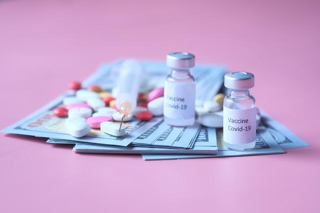 Concetto di costo sanitario con dollaro statunitense, vaccino e pillole. Foto Premium