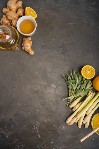 Tè sano antiossidante e antinfiammatorio con ingredienti freschi zenzero, citronella, salvia, miele e limone su sfondo scuro con spazio di copia. vista dall'alto. Foto Premium