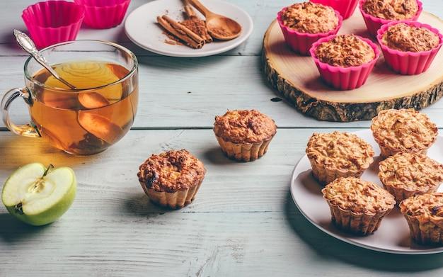 Colazione salutare. muffin di farina d'avena cotta con mela e tazza di tè verde sul tavolo in legno chiaro. Foto Premium