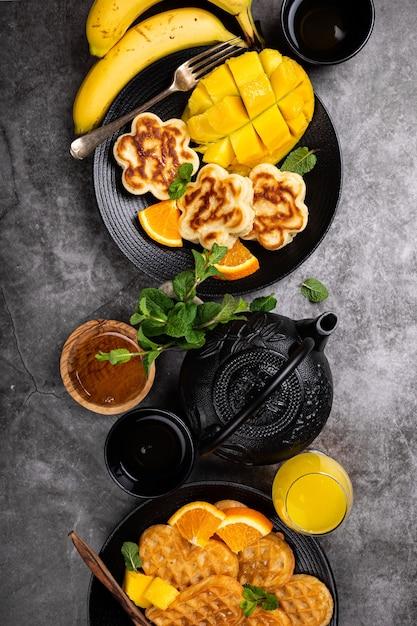 Superficie sana colazione con cuori di waffle caldi freschi, fiori di frittelle con miele di bacche e frutta esotica su grigio, vista dall'alto, piatto laici. concetto di cibo sano con spazio di copia Foto Premium