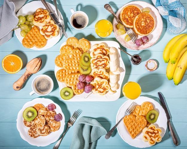 Sana colazione con cuori di cialde calde fresche, fiori di frittelle con marmellata di frutti di bosco e frutta sulla superficie turchese, vista dall'alto, piatto laici concetto di cibo Foto Premium