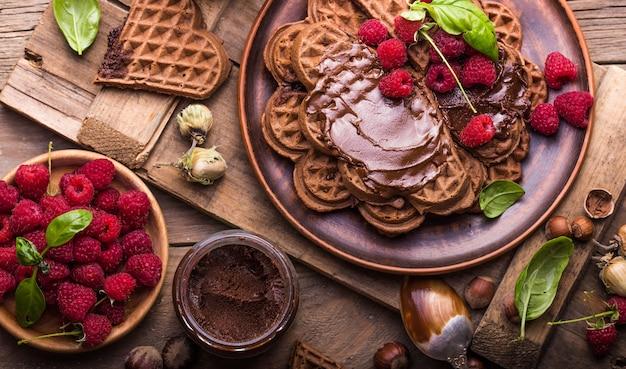 Sana colazione con cuori di cialde calde fresche, frittelle con crema al cioccolato e lampone Foto Premium