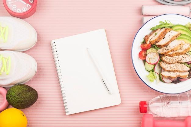 Concetto sano con cibo nutrizionale nella scatola del pranzo e attrezzature per il fitness con la donna che scrive il tempo per rimanere in buona salute sul libro del diario Foto Premium