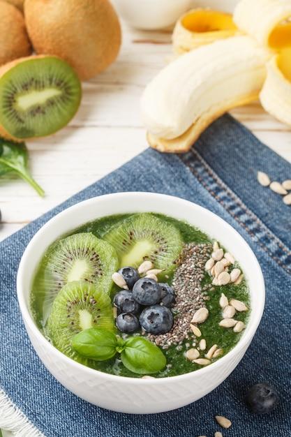 Frullato verde sano e ingredienti: spinaci, banana, kiwi, semi di chia, Foto Premium