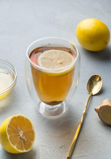 Tè al miele di limone e tè alle erbe di vita sana con radice di zenzero su una superficie grigia Foto Premium