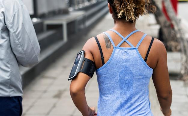 Donna in buona salute che si esercita mentre usando tecnologia Foto Premium