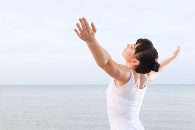 Giovane donna in buona salute respirando e godersi la brezza estiva all'aperto in mare Foto Premium