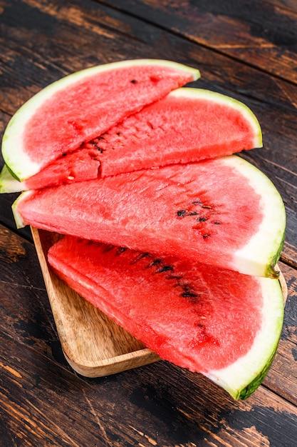 Mucchio di anguria rossa fresca a fette. sfondo in legno scuro. vista dall'alto. Foto Premium