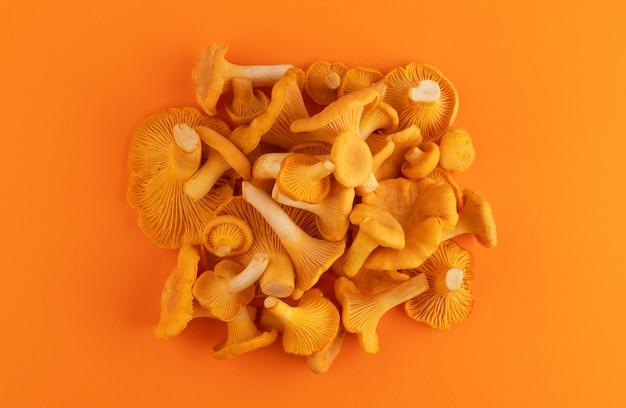 Mucchio di finferli freschi crudi su colore arancione Foto Premium