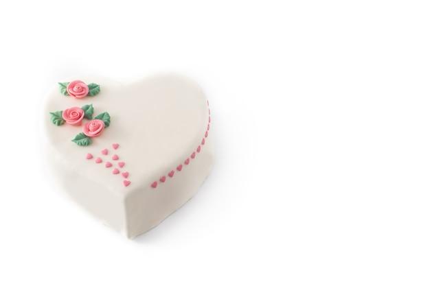 Torta di cuore per san valentino, decorata con rose e cuori di zucchero rosa isolati su sfondo bianco Foto Premium