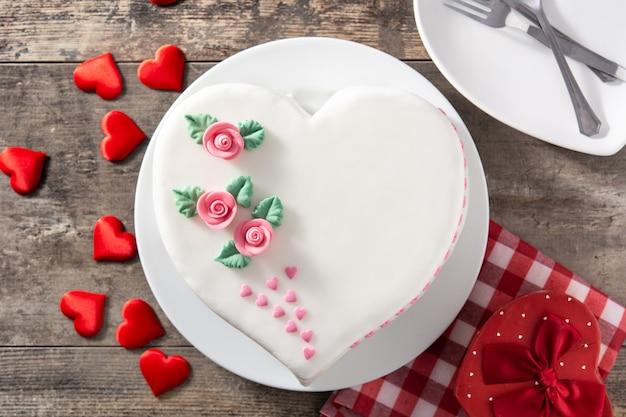 Torta di cuore per san valentino, decorata con rose e cuori di zucchero rosa sulla tavola di legno Foto Premium