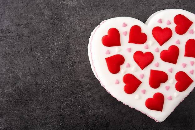 Torta di cuore per il giorno di san valentino, decorata con cuori di zucchero su sfondo nero ardesia Foto Premium