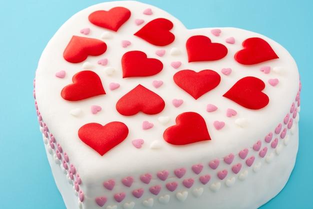 Torta cuore per san valentino, decorata con cuori di zucchero su sfondo blu Foto Premium