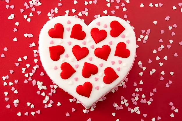 Torta cuore per san valentino, decorata con cuori di zucchero su sfondo rosso Foto Premium