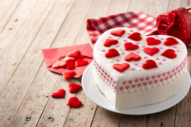 Torta cuore per san valentino decorata con cuori di zucchero sulla tavola di legno Foto Premium