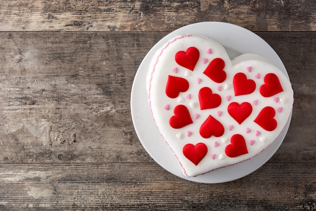 Torta di cuore per san valentino, decorata con cuori di zucchero sulla tavola di legno Foto Premium