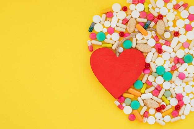 Cuore e pillole colorate su giallo Foto Premium