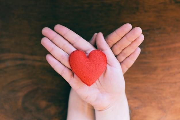 Cuore in mano per il concetto di filantropia - donna con cuore rosso sulle mani per san valentino o donare aiuto dare amore calore prendersi cura di sfondo in legno Foto Premium